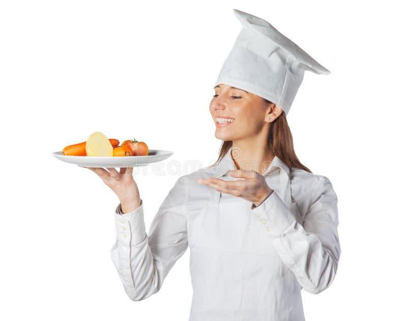 Gelukkige kokvrouw die een schotel met groenten toont royalty-vrije stock fotografie