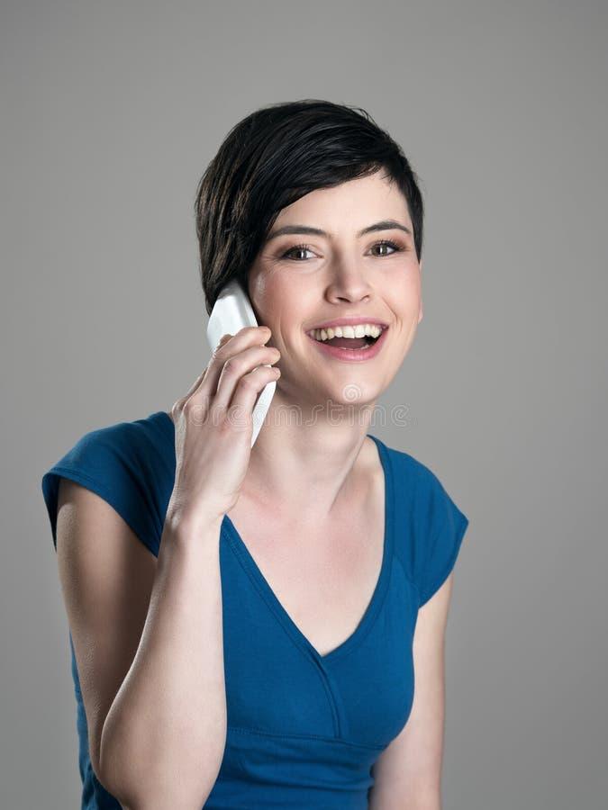 Gelukkige korte haarvrouw die op de mobiele telefoon met toothy glimlach spreken stock fotografie