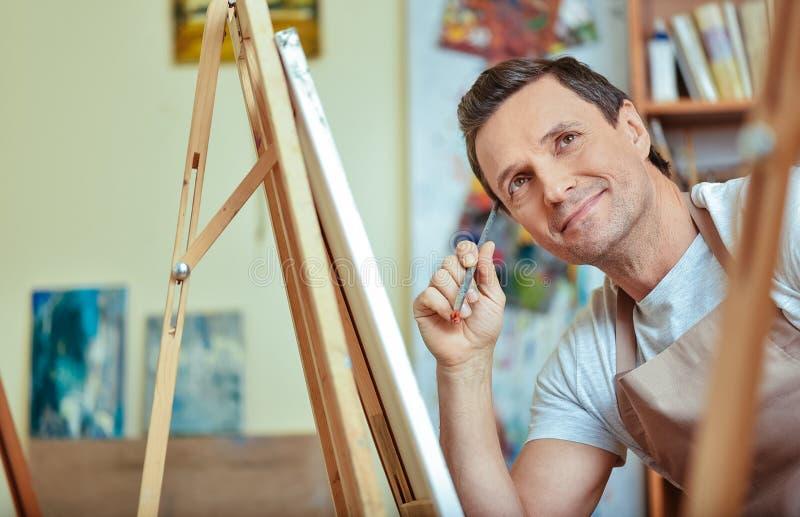 Gelukkige kunstenaar die in het schilderen van studio dromen royalty-vrije stock foto