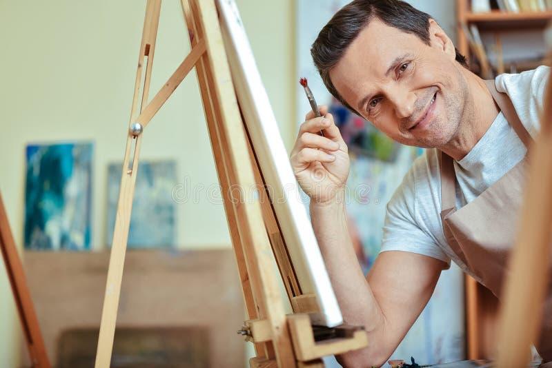 Gelukkige kunstenaar die in het schilderen van studio glimlachen stock foto's