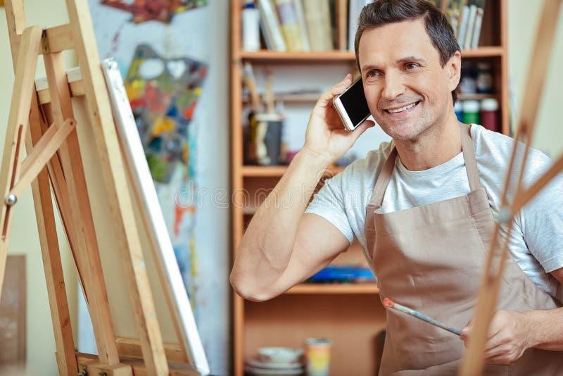Gelukkige kunstenaar die op cellphone in het schilderen van studio spreken stock afbeeldingen