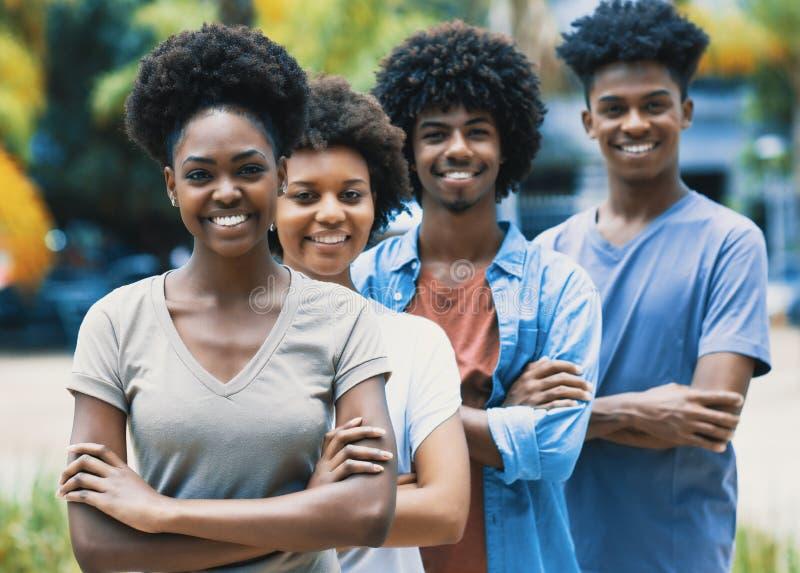 Gelukkige lachende Afrikaanse Amerikaanse jonge volwassenen in lijn stock foto