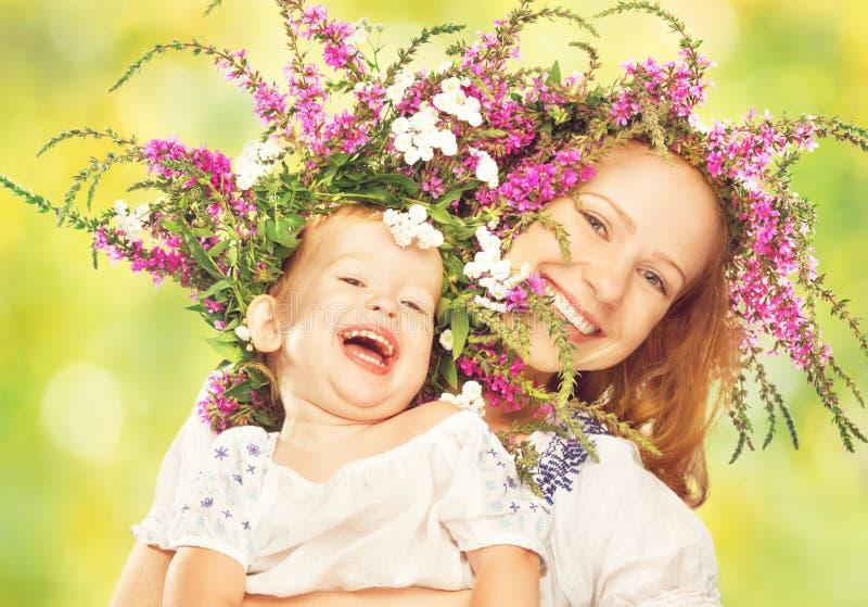 Gelukkige lachende dochter die moeder in kronen van de zomerbloemen koesteren stock afbeelding