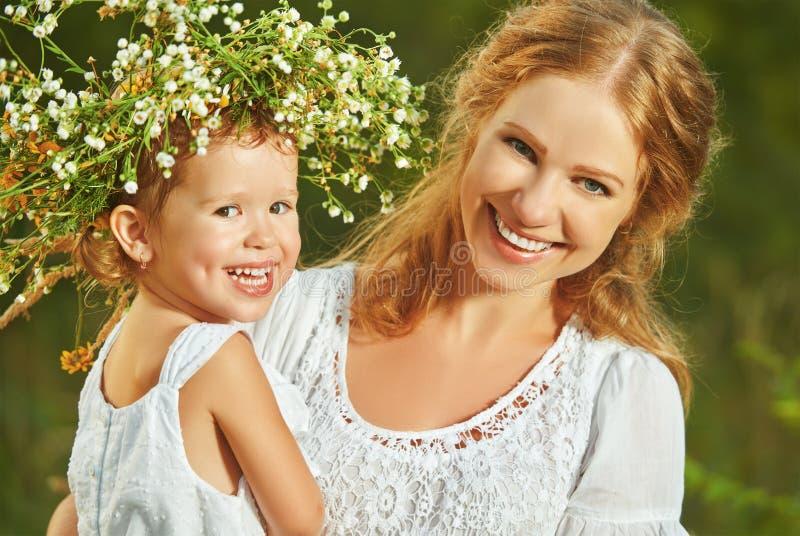 Gelukkige lachende dochter die moeder in kronen van de zomerstroom koesteren stock fotografie