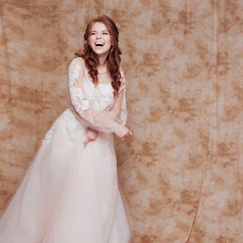 Gelukkige lachende jonge vrouw in huwelijkskleding met lange kokers Jonge redheaded vrouw in huwelijkskleding stock afbeeldingen