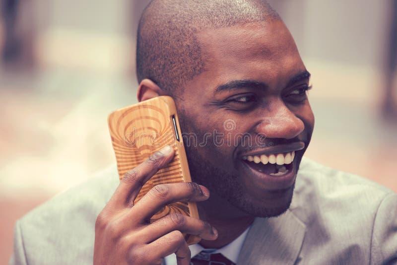 Gelukkige lachende jonge zakenman die op mobiele telefoon in openlucht spreken royalty-vrije stock foto