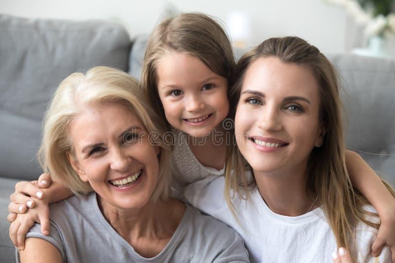 Gelukkige lachende kleindochtermoeder en grootmoeder die camera bekijken stock foto