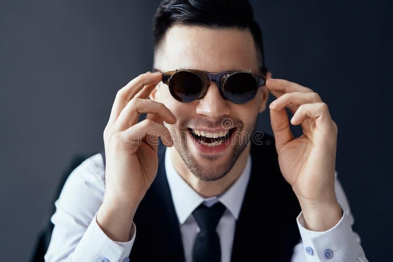 Gelukkige lachende mens in retro zonnebril op zwarte achtergrond royalty-vrije stock afbeelding
