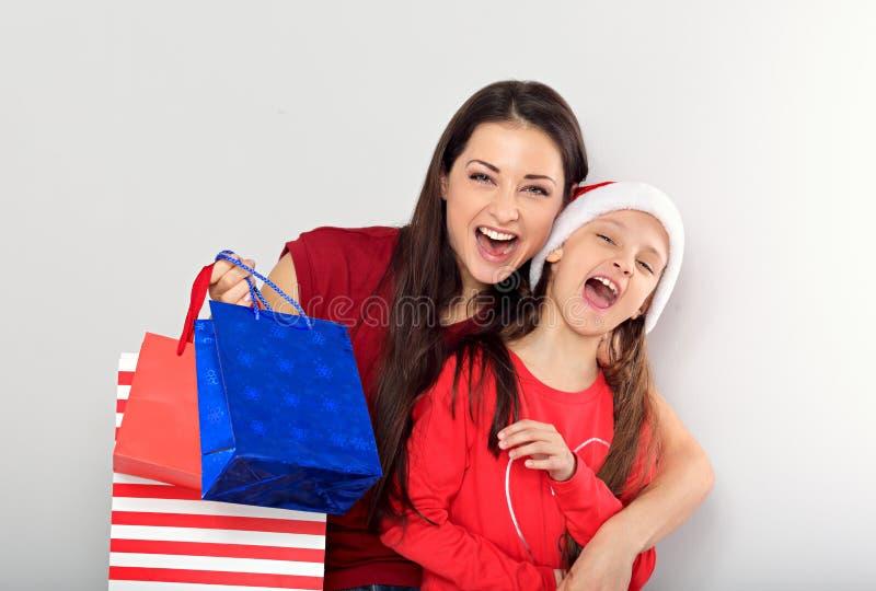 Gelukkige lachende moeder die met open mond met liefde haar leuke joying dochter koesteren royalty-vrije stock fotografie