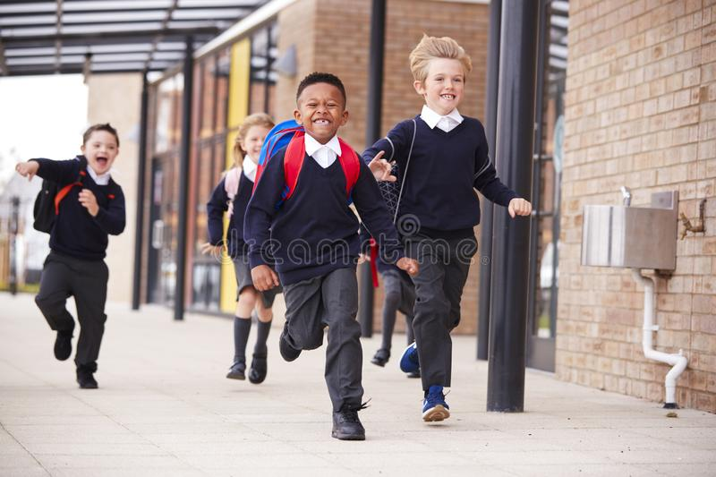 Gelukkige lage schooljonge geitjes, dragend schooluniformen en rugzakken, die op een gang buiten de hun schoolbouw lopen, vooraan royalty-vrije stock foto's