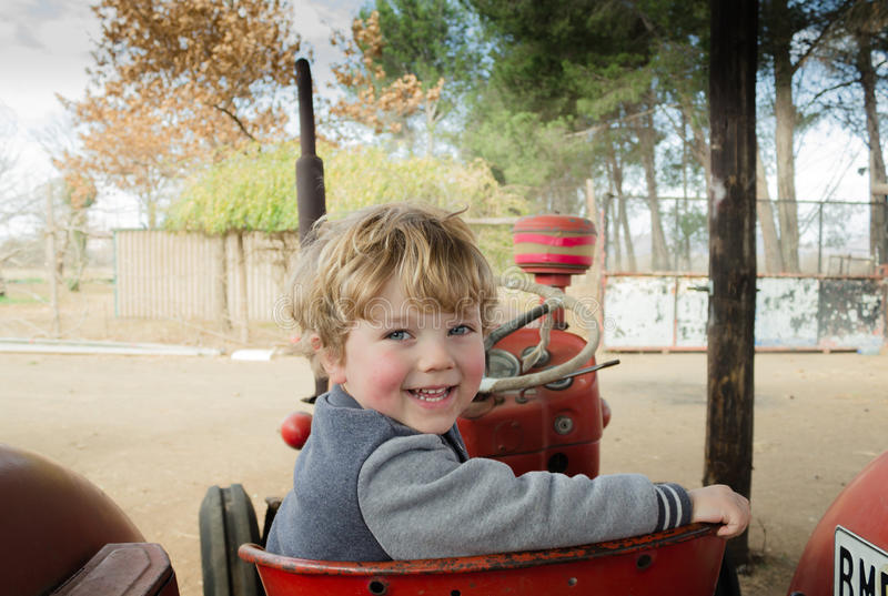 Gelukkige landbouwbedrijfjongen op tractor stock fotografie