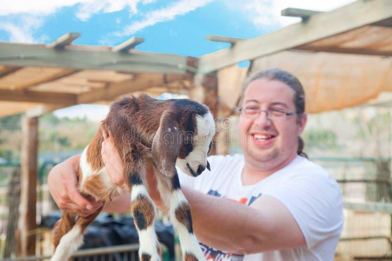 Gelukkige landbouwer met het goatling stock fotografie