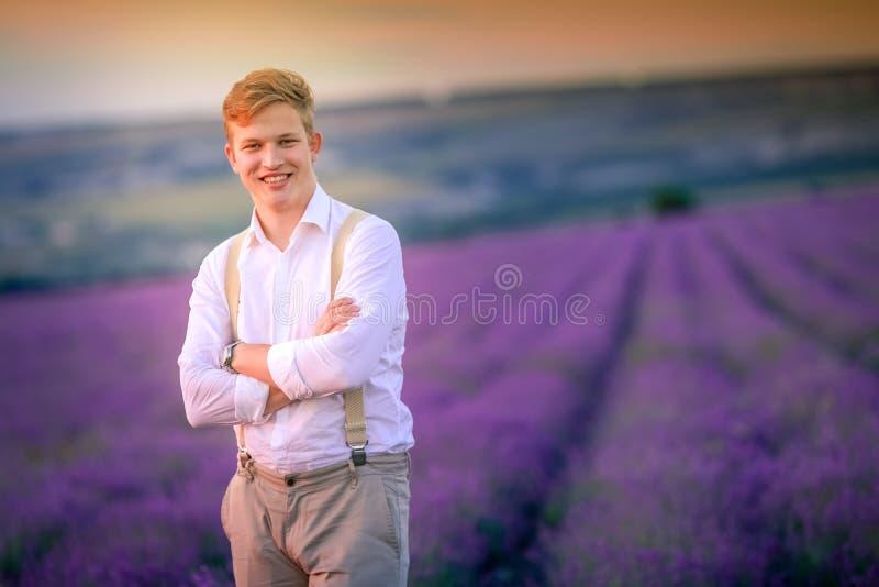 Gelukkige landbouwer in zijn lavendelaanplanting in een zonnige dag stock foto