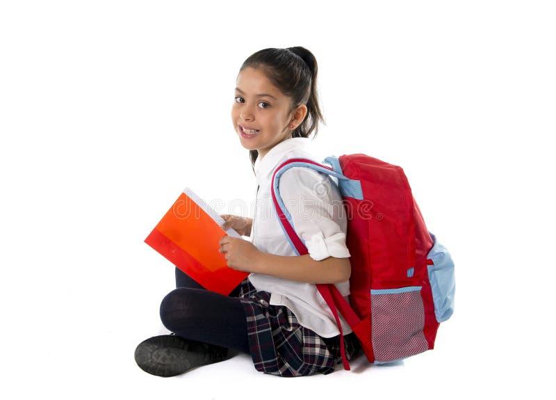 Gelukkige Latijnse van de de lezingshandboek of blocnote van het schoolmeisje het glimlachen zitting op de vloer stock foto's