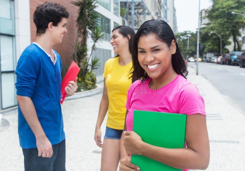 Gelukkige Latijnse vrouwelijke student in roze overhemd met andere studenten stock fotografie