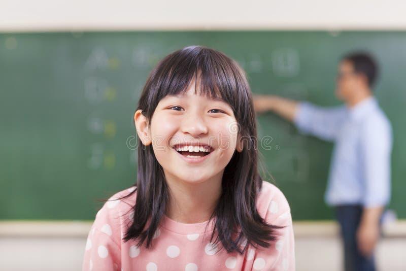 Gelukkige leerlingen die in klasse met leraar glimlachen stock afbeeldingen