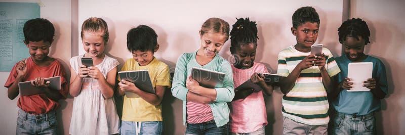 Gelukkige leerlingen die zich met technologie bevinden stock foto