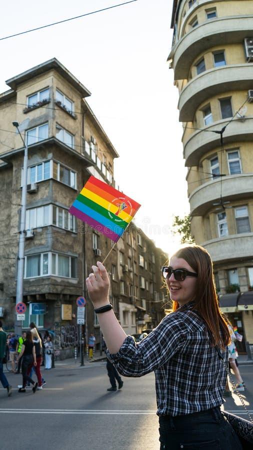 Gelukkige Lesbische vrouw die een regenboogvlag in een Trotsparade, Sofia Pride Festival in de straat golven Rode hoofd trotse zo royalty-vrije stock fotografie
