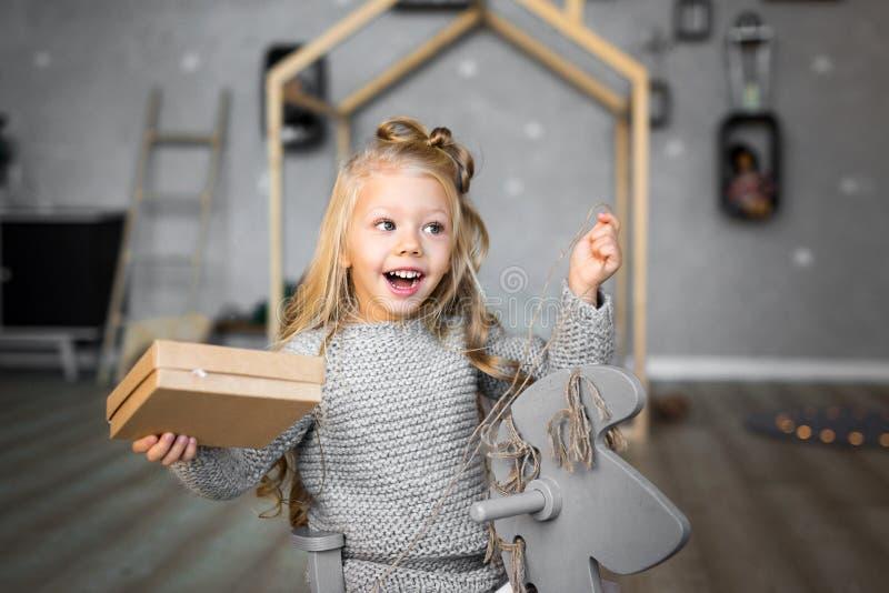 Gelukkige leuk weinig glimlachend meisje met de doos van de Kerstmisgift Vrolijke Kerstmis en gelukkige vakantie royalty-vrije stock foto's
