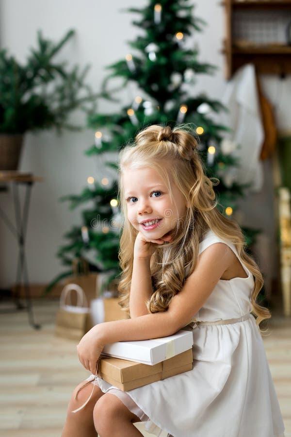 Gelukkige leuk weinig glimlachend meisje met de doos van de Kerstmisgift Vrolijke Kerstmis en gelukkige vakantie royalty-vrije stock fotografie