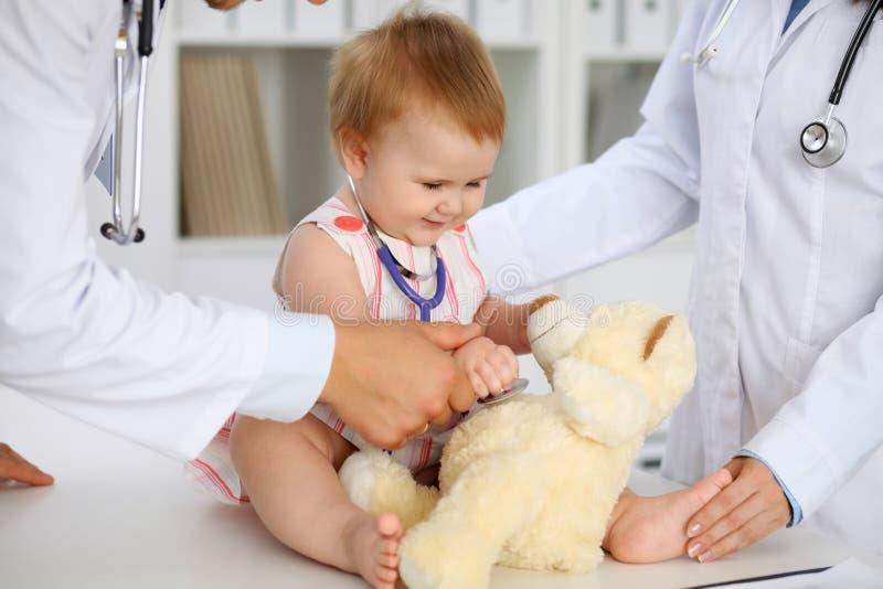 Gelukkige leuke baby bij gezondheidsexamen op artsen` s kantoor Het peutermeisje zit en houdt stethoscoop en teddybeer stock fotografie