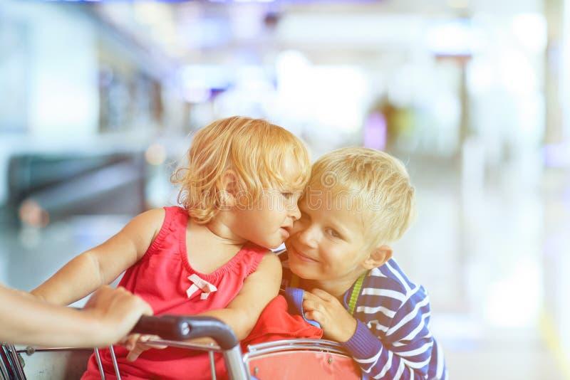 Gelukkige leuke meisje en jongen bij luchthaven op bagagekar royalty-vrije stock fotografie
