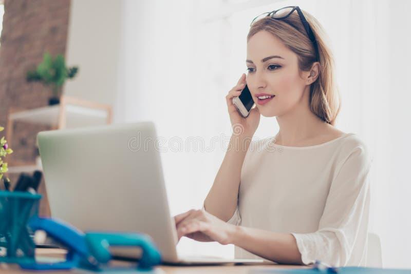 Gelukkige leuke mooie manager die op mobiele telefoon met cliënt mooie aantrekkelijke mooie dame spreken Het zitten bij lijst in  stock afbeeldingen