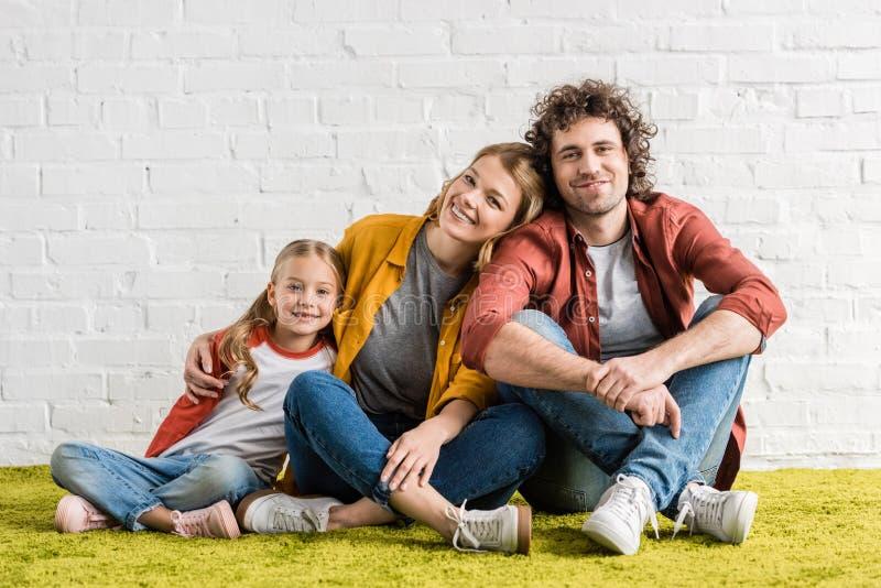 gelukkige leuke ouders met weinig dochter die bij camera glimlachen terwijl samen het zitten stock foto's