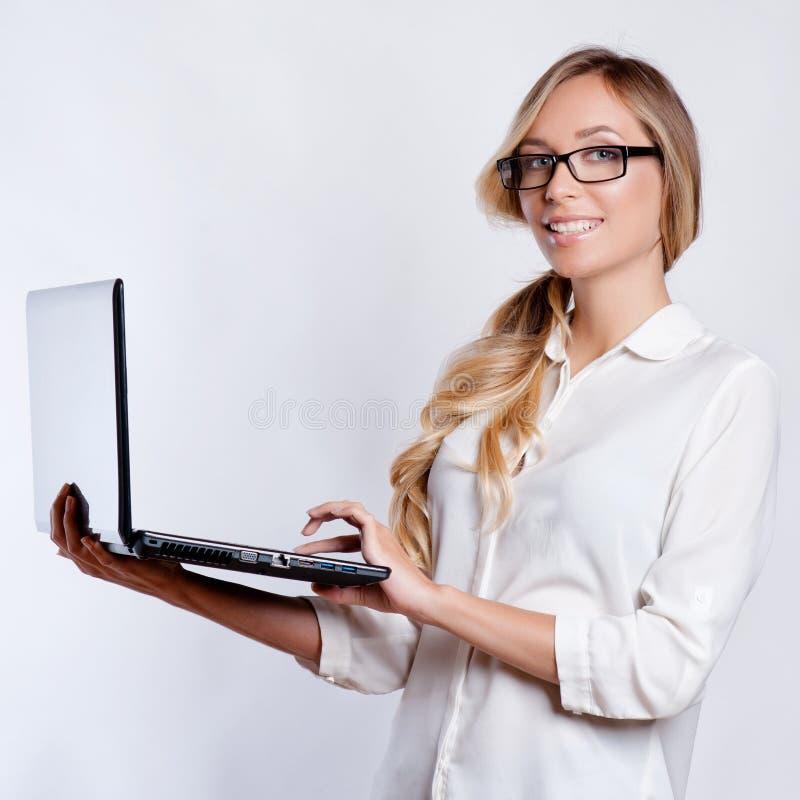 Gelukkige leuke vrouw die lege laptop computer tonen stock fotografie