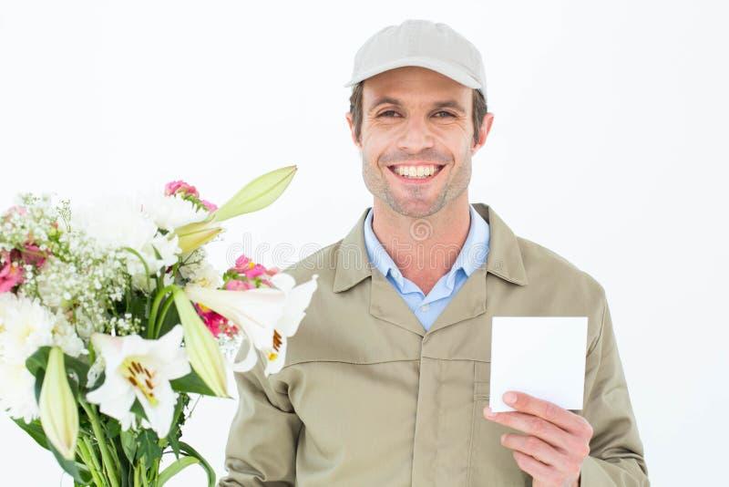Gelukkige leveringsmens met boeket die lege nota tonen royalty-vrije stock foto