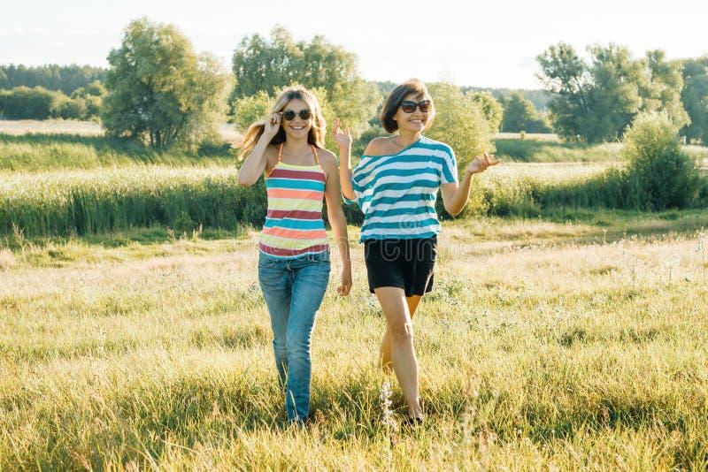 Gelukkige mamma en tiener en dochter die glimlachen spreken Het lopen in aard op een zonnige de zomerdag stock foto's