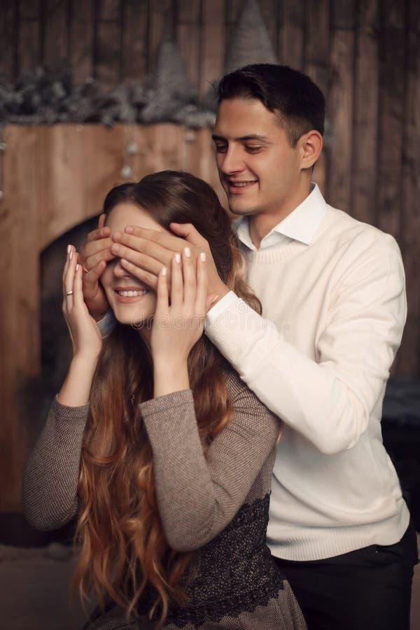 Gelukkige Man die de ogen van de vrouw behandelen met zijn handen Verrast meisje i royalty-vrije stock fotografie