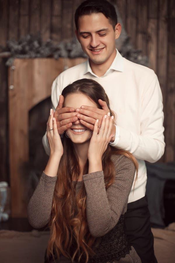 Gelukkige Man die de ogen van de vrouw behandelen met zijn handen Verrast meisje i stock foto's