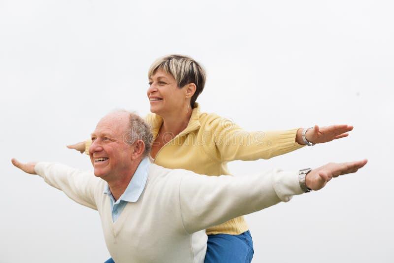 Gelukkige man die op de rug aan vrouw geven stock afbeelding