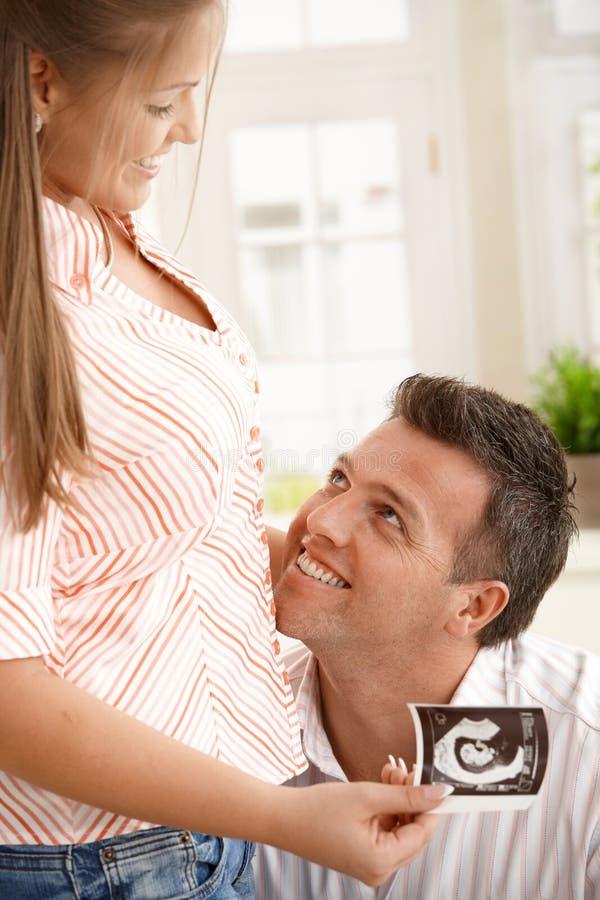 Gelukkige man die zwangere vrouw bekijkt royalty-vrije stock afbeeldingen