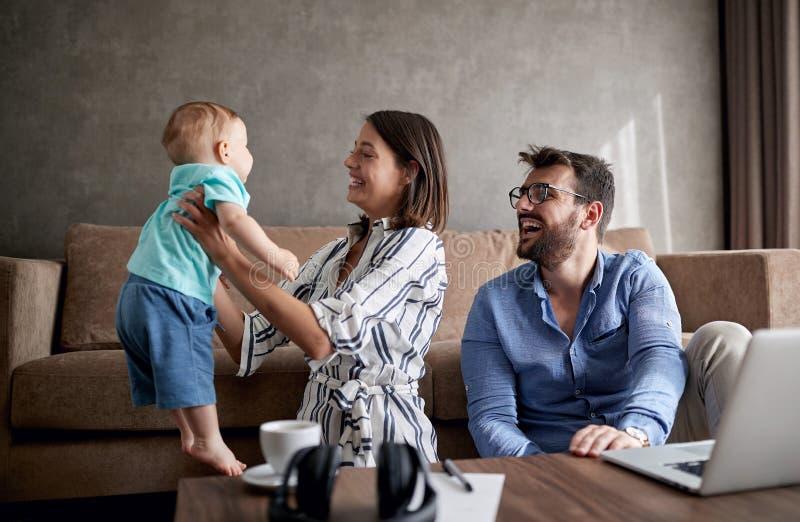 Gelukkige man en vrouw met baby het werken van huis die laptop met behulp van stock afbeeldingen