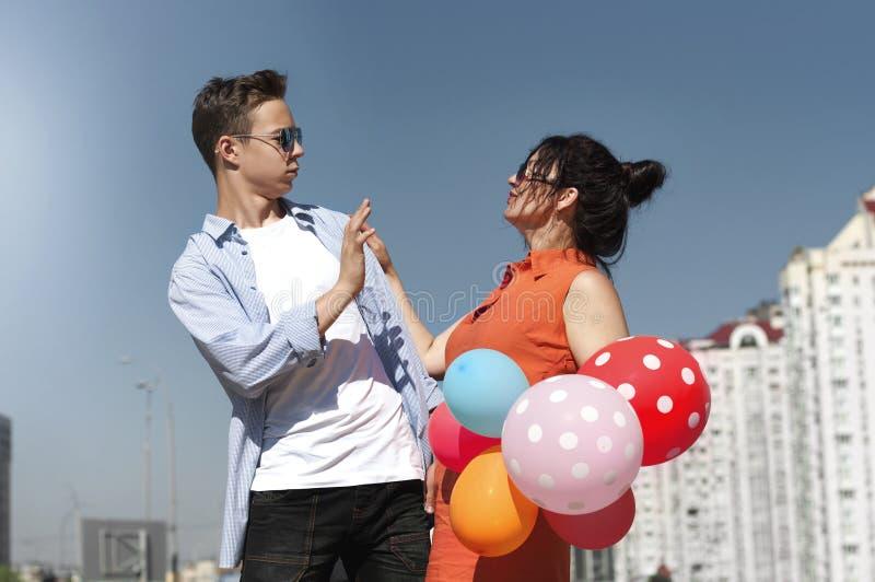 Gelukkige man en vrouw met ballons op de stadsstraat stock afbeelding