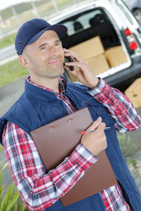 Gelukkige Mannelijke Arbeider in Front Truck Talking On Mobile-Telefoon stock afbeelding
