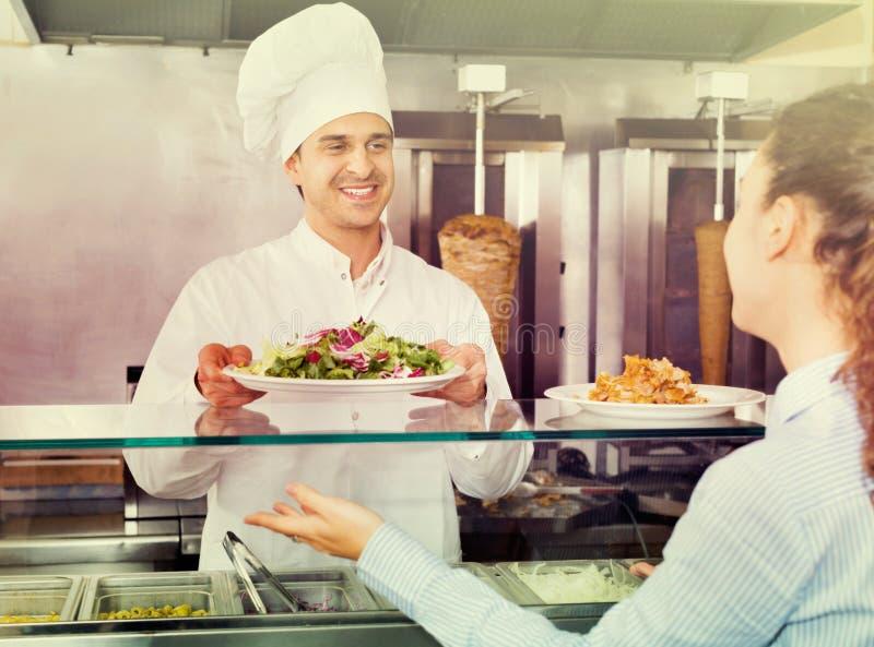 Gelukkige mannelijke arbeiders dienende klant met glimlach op shawarmaplaats royalty-vrije stock fotografie