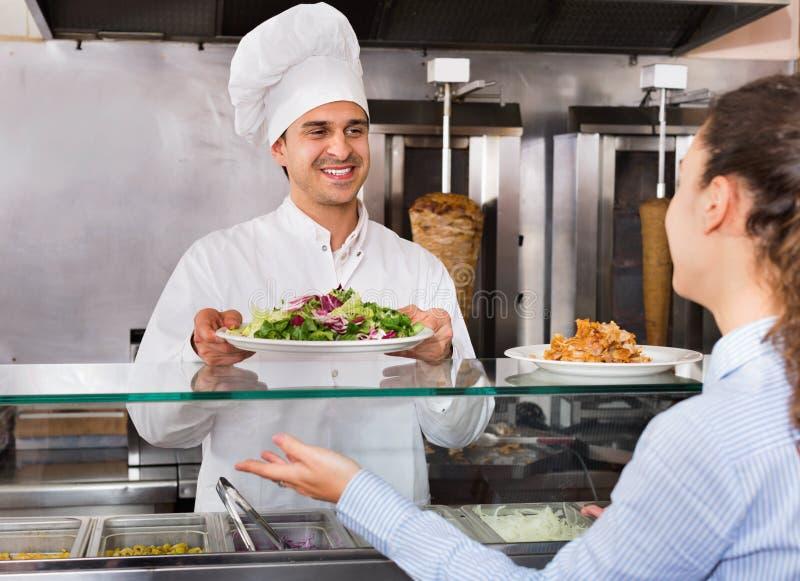 Gelukkige mannelijke arbeiders dienende klant met glimlach op shawarmaplaats royalty-vrije stock afbeelding