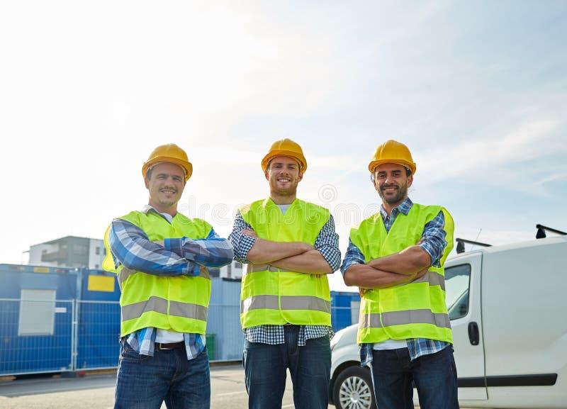 Gelukkige mannelijke bouwers in hoge zichtbare vesten in openlucht stock fotografie