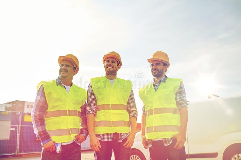 Gelukkige mannelijke bouwers in hoge zichtbare vesten in openlucht royalty-vrije stock foto's