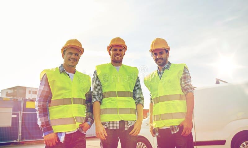 Gelukkige mannelijke bouwers in hoge zichtbare vesten in openlucht stock afbeeldingen