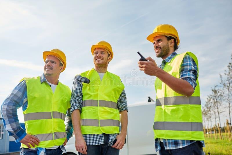 Gelukkige mannelijke bouwers in vesten met walkie-talkie royalty-vrije stock afbeelding