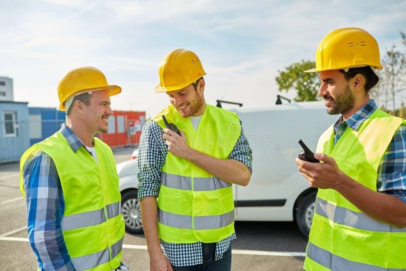 Gelukkige mannelijke bouwers in vesten met walkie-talkie stock fotografie