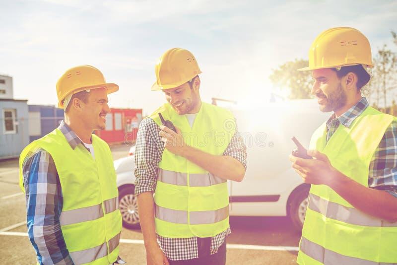 Gelukkige mannelijke bouwers in vesten met walkie-talkie royalty-vrije stock afbeeldingen