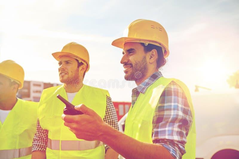 Gelukkige mannelijke bouwers in vesten met walkie-talkie stock foto