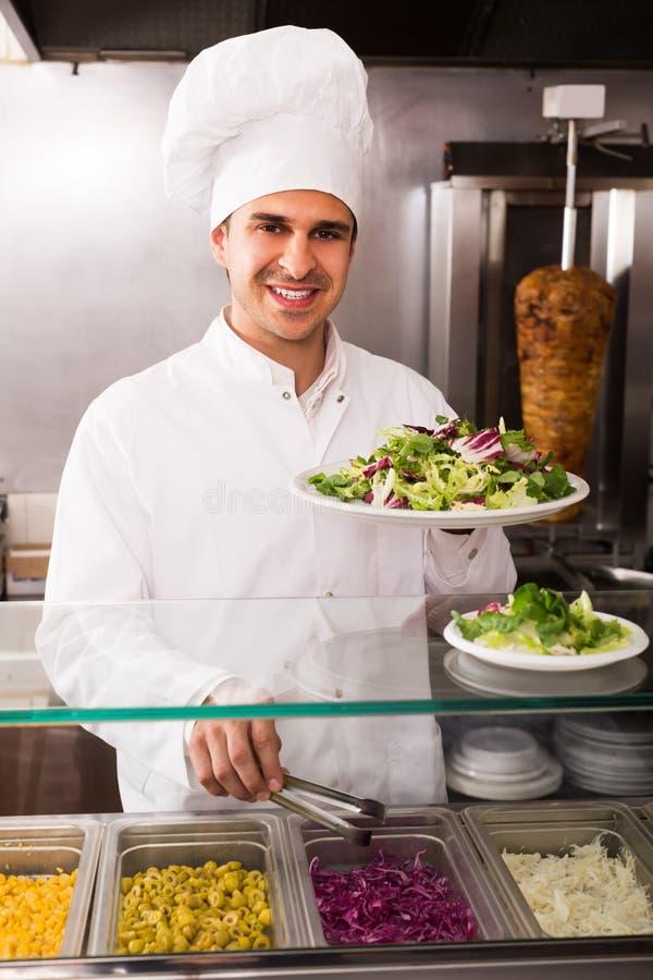 Gelukkige mannelijke chef-kok met groenten stock afbeelding