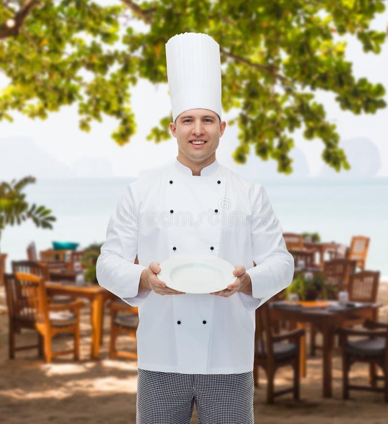 Gelukkige mannelijke chef-kokkok die lege plaat tonen royalty-vrije stock afbeelding