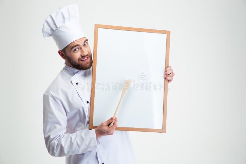 Gelukkige mannelijke chef-kokkok die lege raad houden royalty-vrije stock fotografie